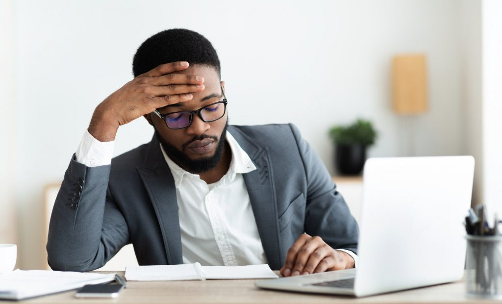Tired african businessman sitting at workplace frustrated by business failure