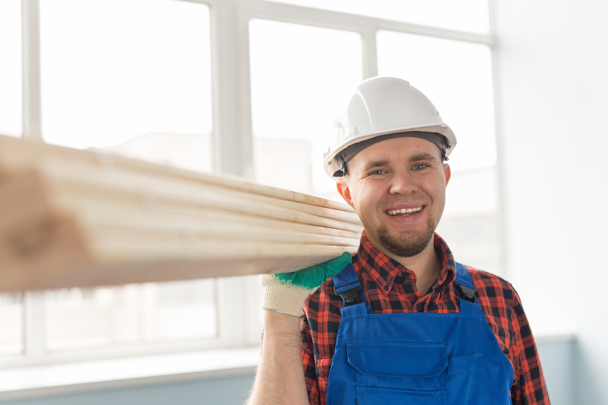 Portrait of handsome male builder laughing infront of window